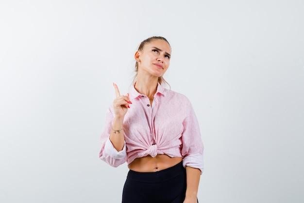 Jeune femme pointant vers le haut en chemise, pantalon et à la pensif. vue de face.