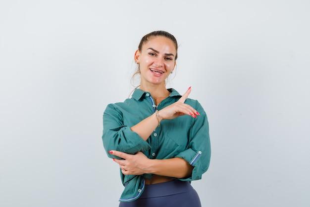 Jeune femme pointant vers le haut en chemise, pantalon et semblant joyeuse, vue de face.