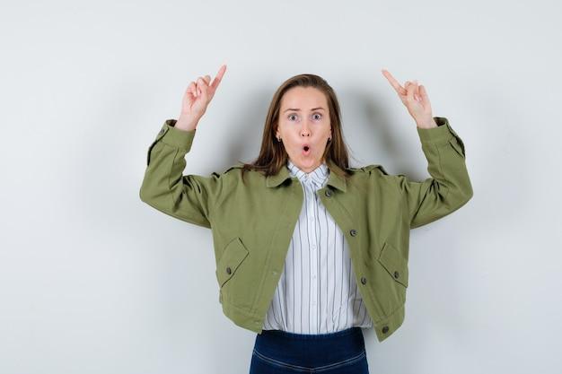 Jeune femme pointant vers le haut en chemise, veste et semblant étonnée, vue de face.