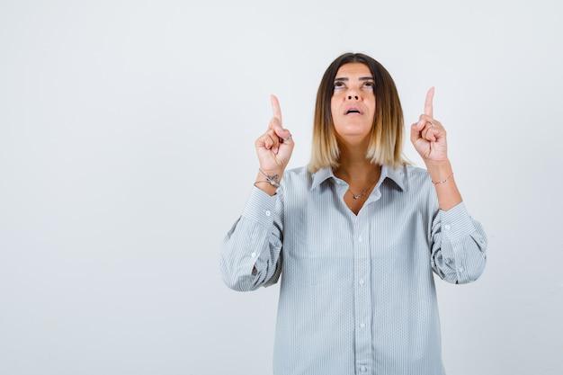 Jeune femme pointant vers le haut dans une chemise surdimensionnée et ayant l'air confiante, vue de face.
