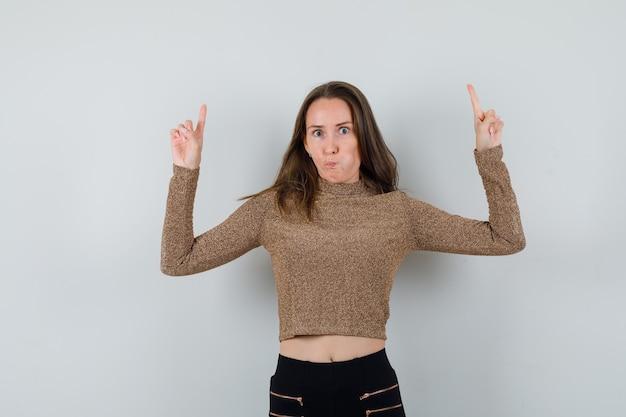 Jeune femme pointant vers le haut avec les deux index en pull doré et pantalon noir et à heureux