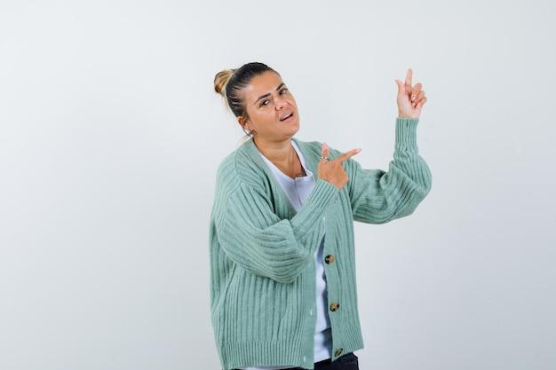 Jeune femme pointant vers le haut et à droite en chemise blanche et cardigan vert menthe et l'air heureux