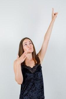 Jeune femme pointant vers le haut en étirant le bras en maillot noir et à la concentration