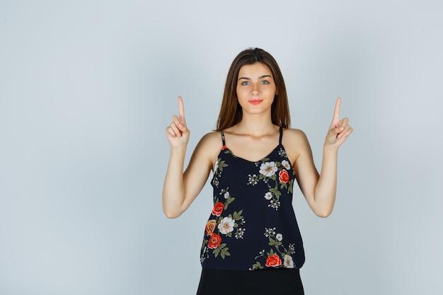 Jeune femme pointant vers le haut en haut floral et à la confiance