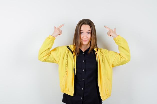 Jeune femme pointant vers le haut avec l'index et l'air heureux