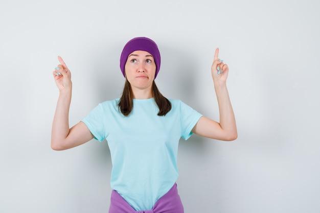 Jeune femme pointant vers le haut avec l'index en t-shirt bleu, bonnet violet et l'air mignon, vue de face.