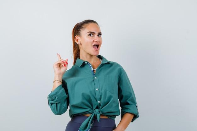 Jeune femme pointant vers le haut, montrant le geste eurêka en chemise verte et l'air intelligent. vue de face.