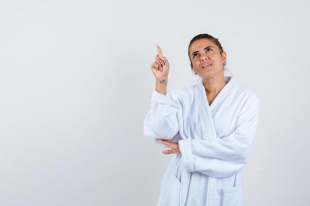 Jeune femme pointant vers le haut en peignoir et à la confiance