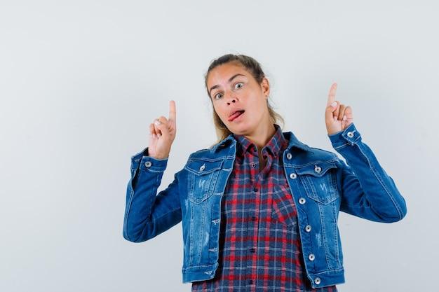 Jeune femme pointant vers le haut, qui sort la langue en chemise, veste et à la confusion, vue de face.
