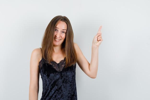 Jeune femme pointant vers le haut et riant en maillot noir