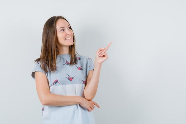 Jeune femme pointant vers le haut en t-shirt et à la béatitude. vue de face.