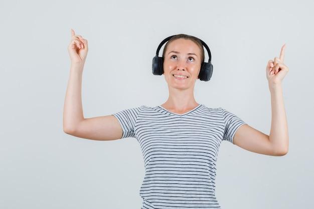 Jeune femme pointant vers le haut en t-shirt, écouteurs et à la recherche d'espoir, vue de face.