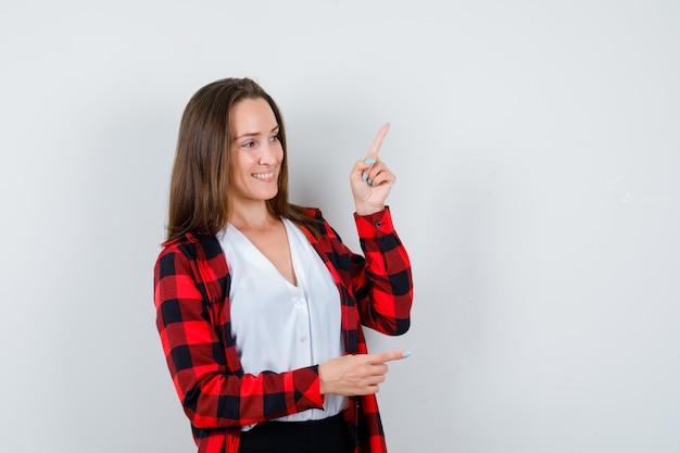 Jeune femme pointant vers le haut et vers la droite, regardant loin dans des vêtements décontractés et semblant joyeuse. vue de face.