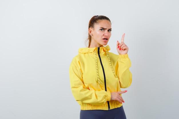 Jeune femme pointant vers le haut en veste jaune et semblant anxieuse. vue de face.