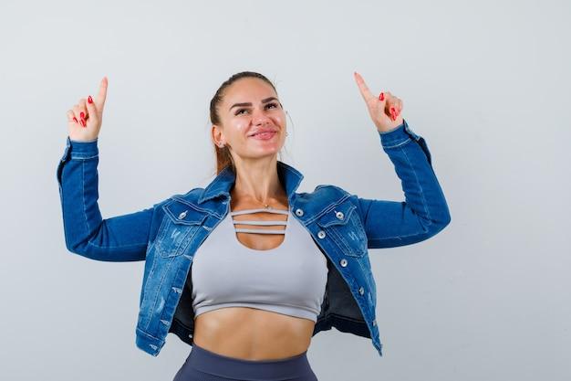 Jeune femme pointant vers le haut, veste en jean et joyeuse. vue de face.