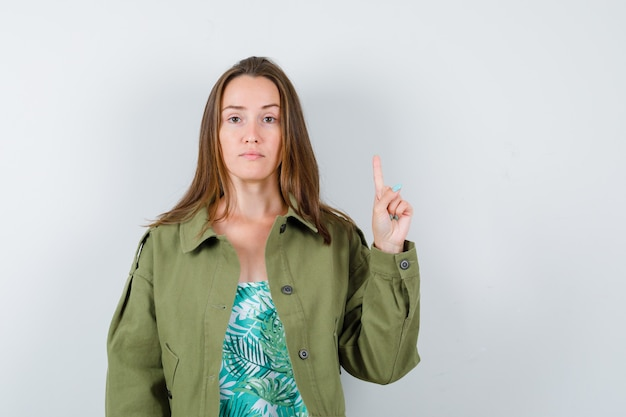 Jeune femme pointant vers le haut en veste verte et semblant confiante. vue de face.