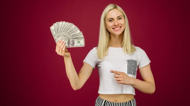 Jeune femme pointant vers une pile d'argent avec son doigt isolé sur fond rubis