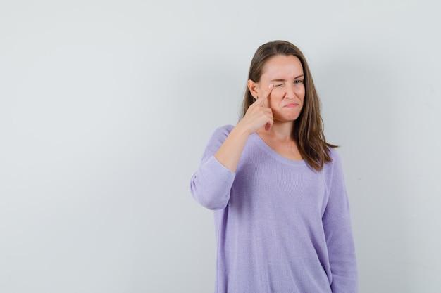 Jeune femme pointant vers sa paupière tout en clignant de l'œil en chemisier lilas et à la recherche concentrée