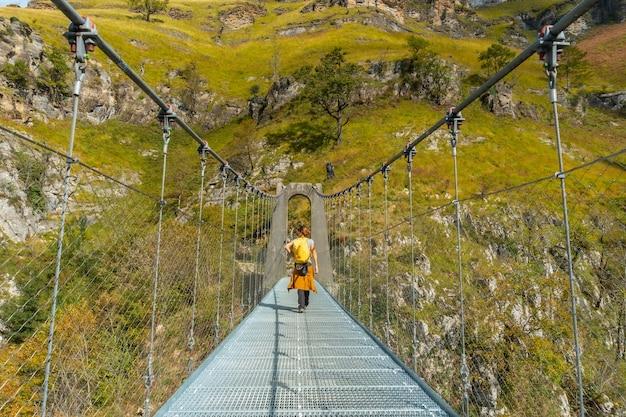 Une jeune femme sur le pont suspendu holtzarte, larrau. dans la forêt ou jungle d'irati, au nord de la navarre en espagne et dans les pyrénées-atlantiques de france