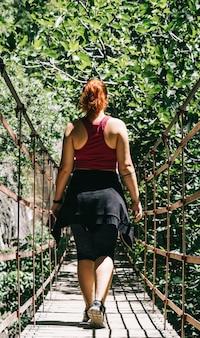 Jeune femme sur un pont suspendu marchant sur la route de los cahorros, grenade, espagne