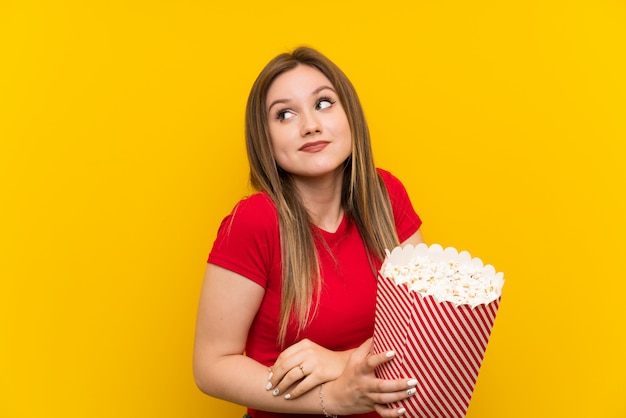 Jeune femme avec des pop-corn sur mur rose faisant des gestes de doutes tout en soulevant les épaules