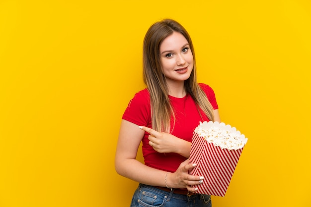 Jeune femme avec des popcorns sur un mur rose pointant sur le côté pour présenter un produit