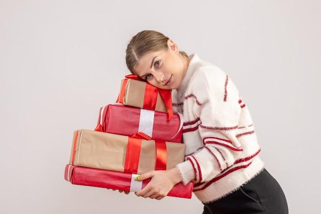 Jeune femme portant des cadeaux de noël sur blanc