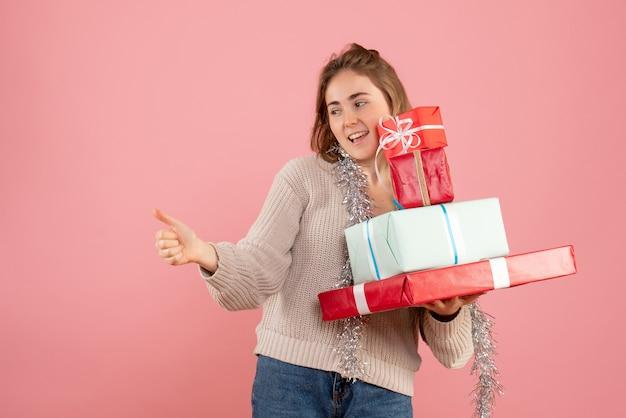 Jeune femme portant des cadeaux de noël sur rose