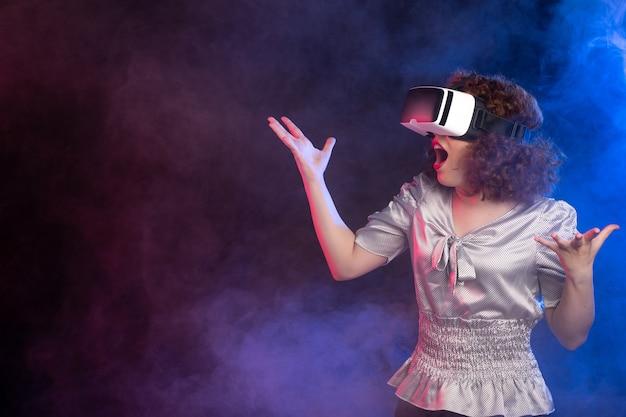 Jeune femme portant un casque de réalité virtuelle sur une surface bleu foncé