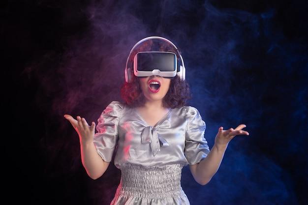 Jeune femme portant un casque vr dans des écouteurs sur une surface sombre