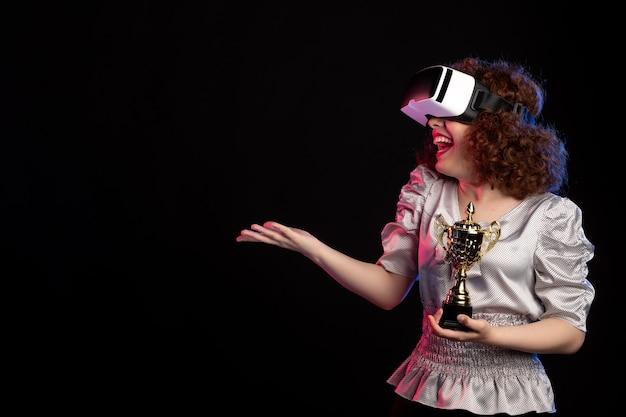 Jeune femme portant un casque vr avec une tasse sur un jeu vidéo sombre jouer à la vision de jeu