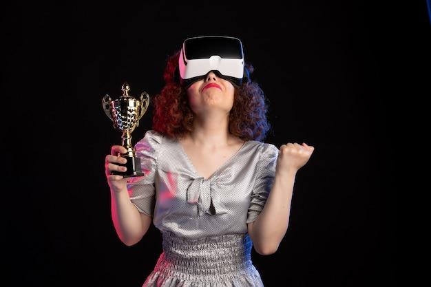 Jeune femme portant un casque vr avec une tasse sur un sol sombre jeu de vision de jeux vidéo