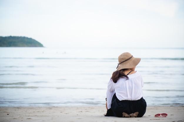 Jeune femme portant un chapeau assis sur la plage face à la mer et avoir des lunettes placées sur le côté.