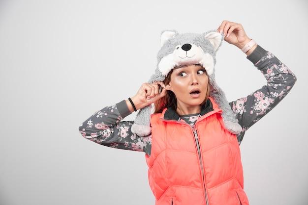 Jeune femme portant un chapeau drôle sur un mur blanc.