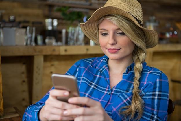Jeune femme portant un chapeau tout en utilisant un téléphone mobile dans un café