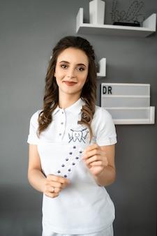 Jeune femme portant un costume médical et posant à la caméra. portrait de dentiste souriant. médecin heureux tenant des outils dans les mains.