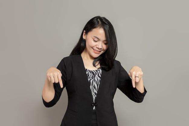 Jeune femme portant un costume noir pointant et regardant vers le bas