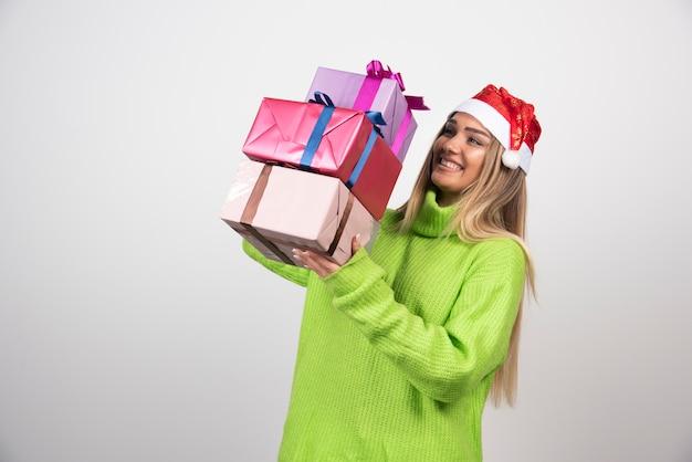 Jeune femme portant dans les mains des cadeaux de noël festifs.