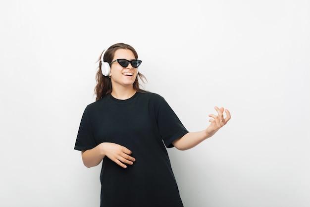 Jeune femme portant des écouteurs joue une guitare imaginative.