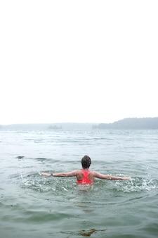 Jeune femme portant haut brillant nageant dans le lac brumeux le jour de pluie.