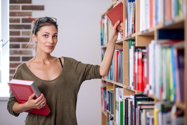 Jeune femme portant des lunettes prendre un livre sur une étagère dans une bibliothèque.