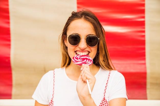 Jeune femme portant des lunettes de soleil mordant sucette