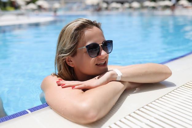 Jeune femme portant des lunettes de soleil se reposant au bord de la piscine