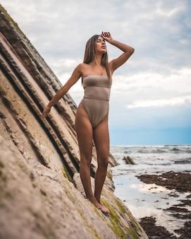 Jeune femme portant un maillot de bain gris et posant de façon spectaculaire sur le rivage entouré de rochers