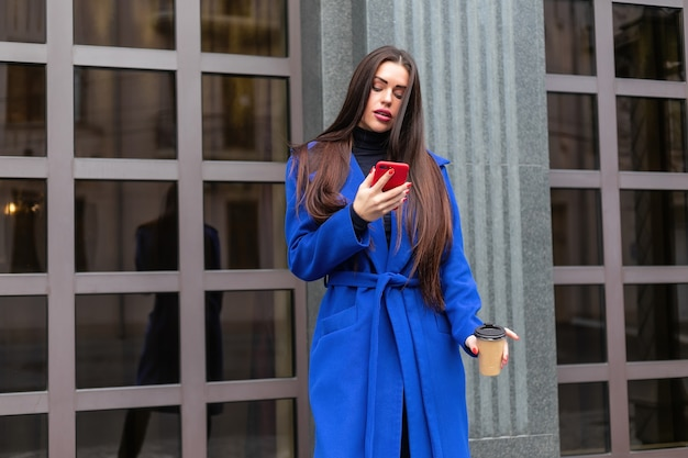 Une jeune femme portant un manteau bleu boit du café pour aller parler au téléphone dans la rue. tir moyen verrouillé en temps réel