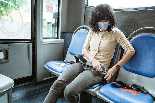 Jeune femme portant un masque est assis sur un banc tout en attachant la ceinture de sécurité avant de partir dans le bus