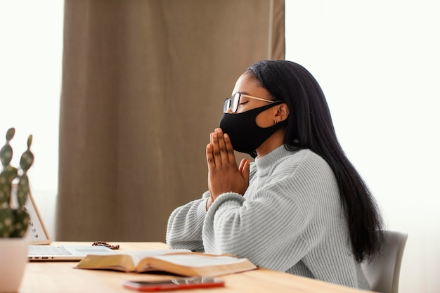 Jeune femme portant un masque facial en priant