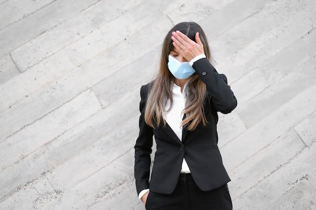 Jeune femme portant un masque facial et vérifiant sa température