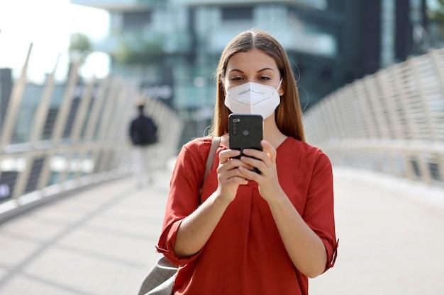 Jeune femme portant un masque kn95 ffp2 à l'aide de l'application de téléphone intelligent dans la rue de la ville moderne