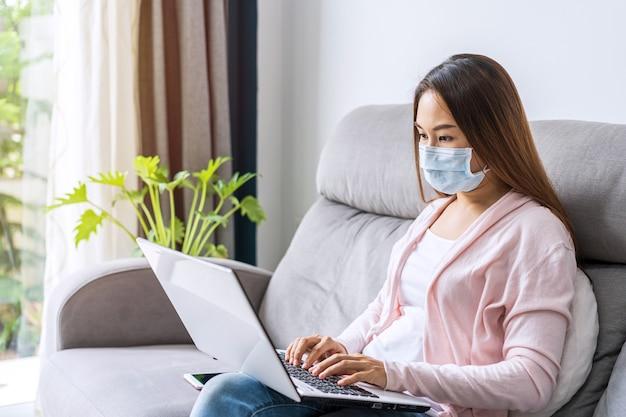 Jeune femme portant un masque médical assis au salon et travaillant sur un ordinateur portable à la maison